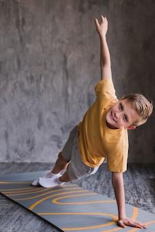 Menino de aptidão exercício no colchonete na frente do muro de concreto