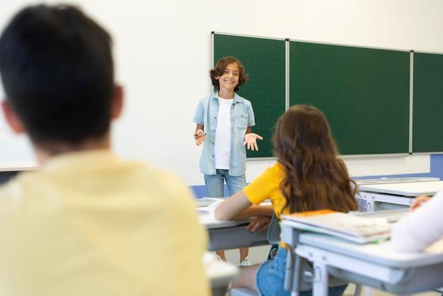 Menino de baixo ângulo, apresentando na frente da classe