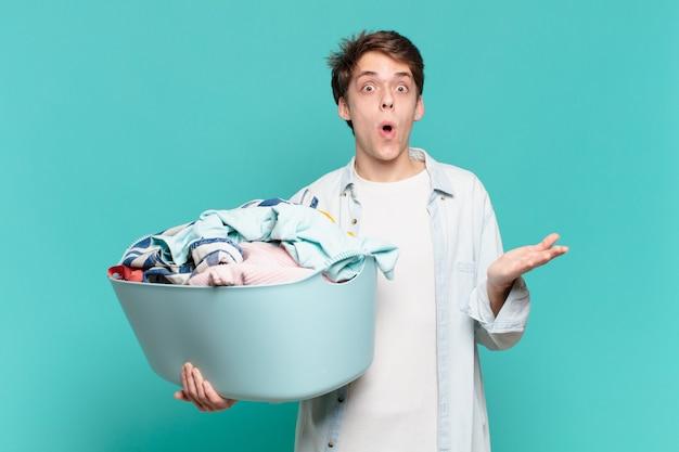 Menino de boca aberta e pasmo, chocado e surpreso com um conceito incrível de lavar roupas