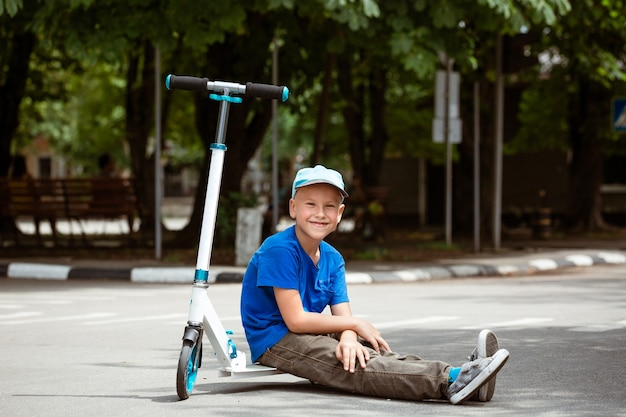 Menino de boné sentado em uma scooter no parque em um dia ensolarado de verão