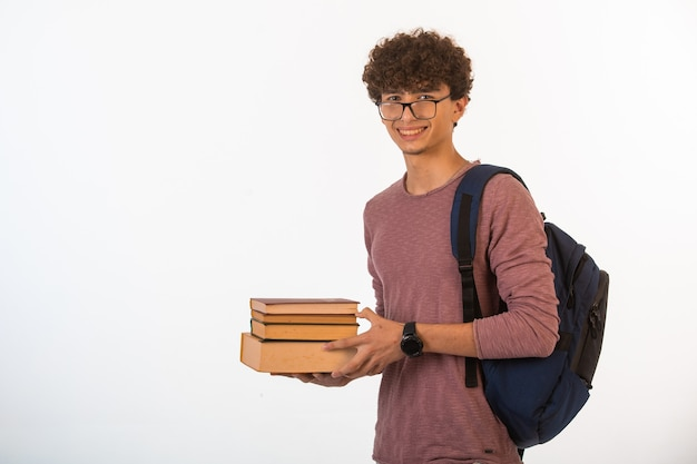Menino de cabelo encaracolado em óculos optique segurando livros escolares com as duas mãos e sorrindo.
