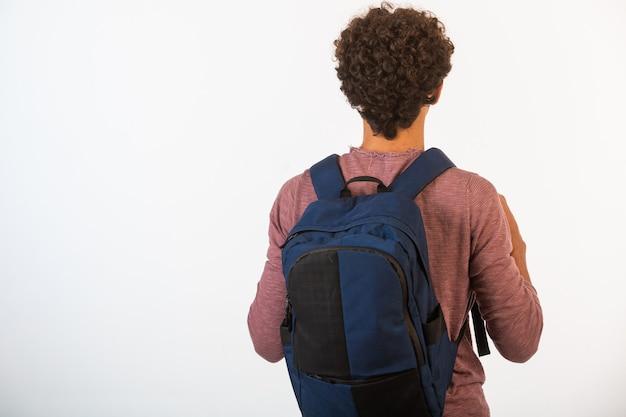 Menino de cabelo encaracolado em óculos optique segurando sua mochila, vista de trás.
