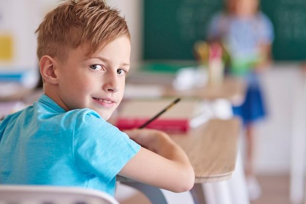Menino de cabelo loiro durante a aula