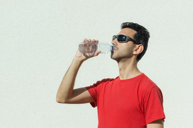 Menino de cabelos escuros, bebendo água mineral