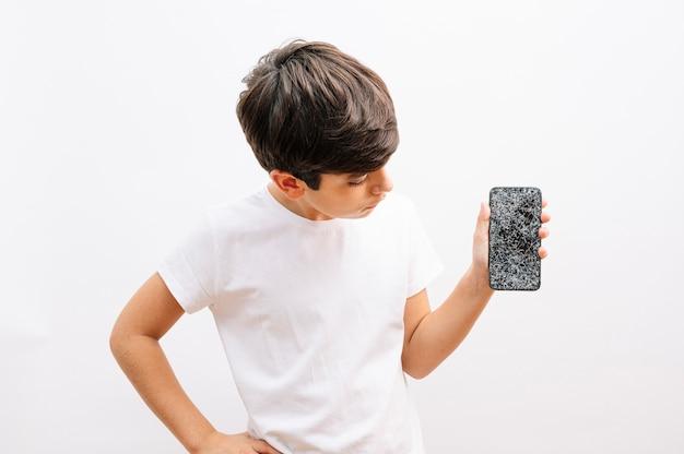 Menino de cabelos escuros preocupado olhando para o telefone inteligente com a mão chocada por engano, vergonha, expressão de medo, medo em silêncio, conceito secreto