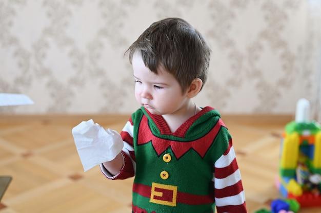 Menino de cabelos escuros usando um lenço de papel para limpar o nariz de um resfriado ou alergias ao pólen.