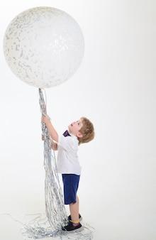 Menino de camisa branca segura um grande balão grande balão branco celebração conceito festa humor cópia espaço para