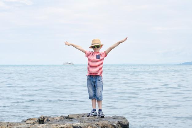 Menino de camiseta listrada e óculos escuros em pé com as mãos ao alto contra o fundo do mar