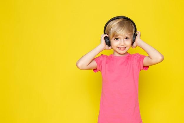 Menino de camiseta rosa e fones de ouvido pretos, ouvindo música