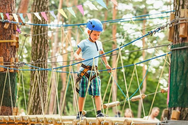 Menino de cinco anos no caminho de corda na floresta