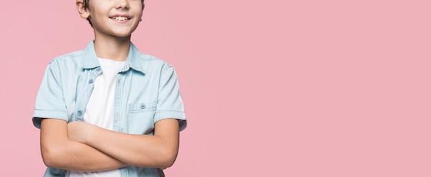 Menino de close-up em pé com os braços cruzados