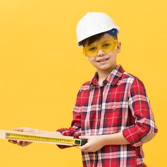 Menino de construção usando fita métrica