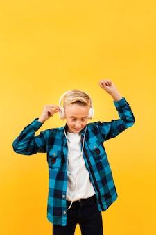 Menino de cópia-espaço com fones de ouvido