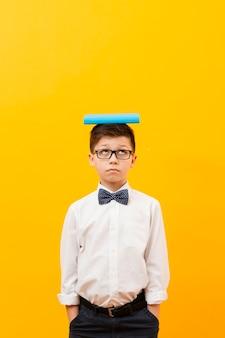 Menino de cópia-espaço com livro na cabeça