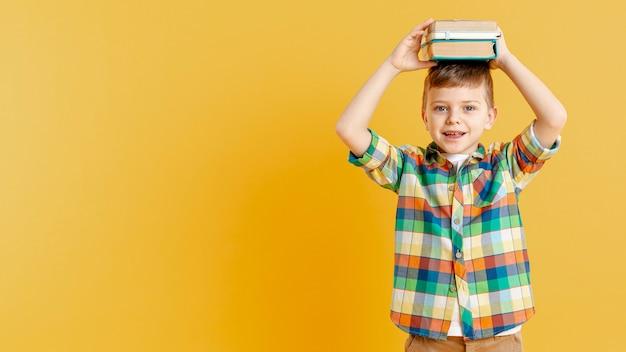 Menino de cópia-espaço com livros na cabeça