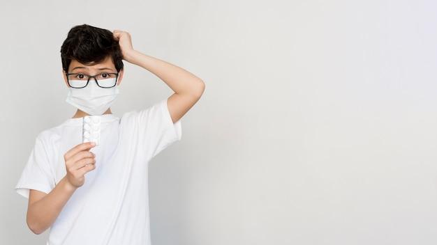 Menino de cópia-espaço com máscara