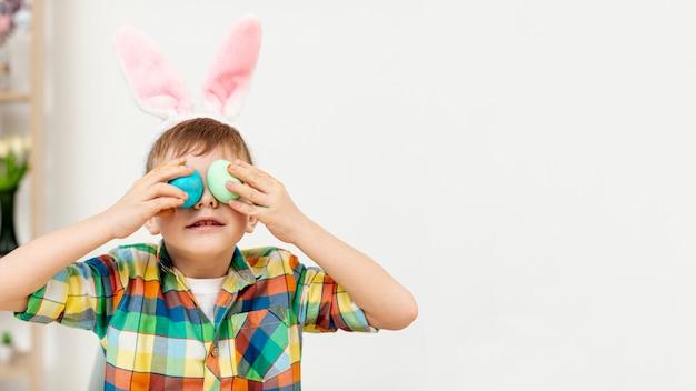Menino de cópia-espaço com ovos pintados