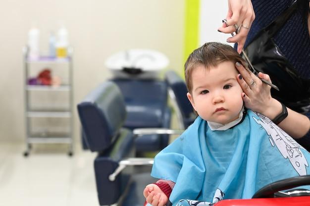 Menino de corte de cabelo 0-1 anos. o primeiro corte de cabelo da criança no cabeleireiro. criança de bebê corte de cabelo.
