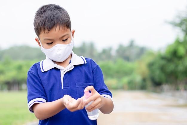 Menino de criança asiática jovem usando máscara de tecido e segurando o frasco de spray de álcool na mão para prevenir a doença de coronavírus ou covid-19.
