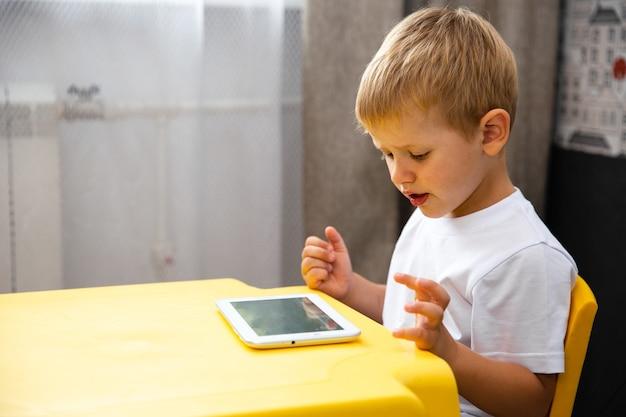 Menino de criança brincando ou assistir desenhos animados sobre o tablet interno.