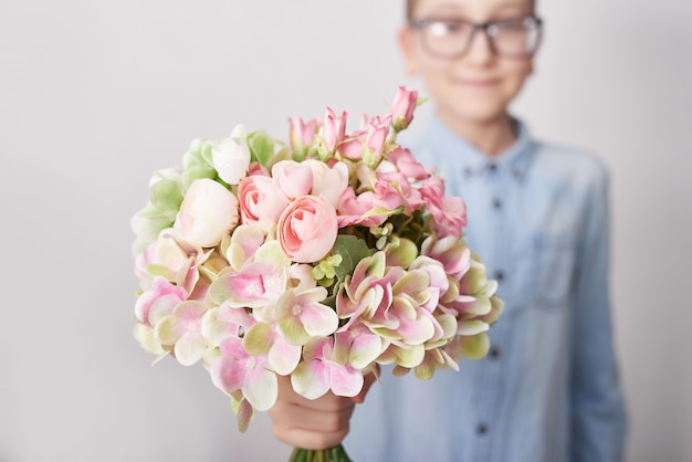 Menino de criança com buquê de flores. dia das mães