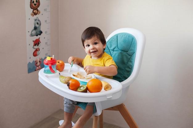 Menino de criança com cabelo escuro em uma camiseta amarela, senta-se em uma cadeira alta e janta frutas.