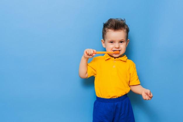 Menino de criança criança feliz escovando os dentes com escova de dentes. cuidados de saúde, higiene dentária.