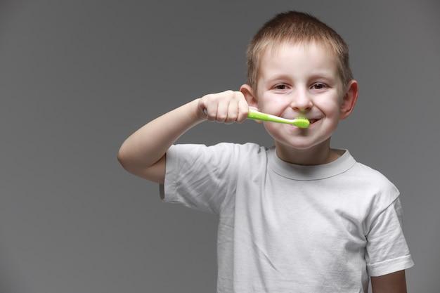Menino de criança criança feliz escovando os dentes com escova de dentes em fundo cinza. cuidados de saúde, higiene dentária. maquete, copie o espaço.