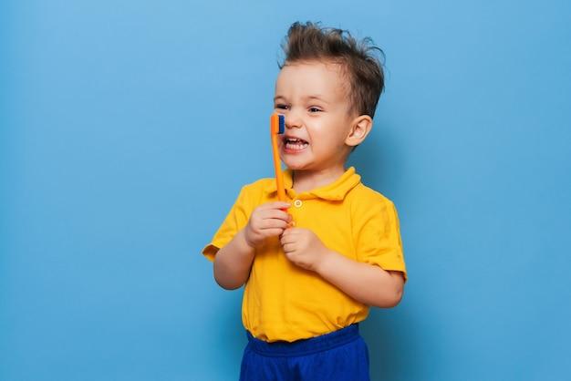Menino de criança criança feliz escovando os dentes com escova de dentes sobre fundo azul. cuidados de saúde, higiene dentária. brincar