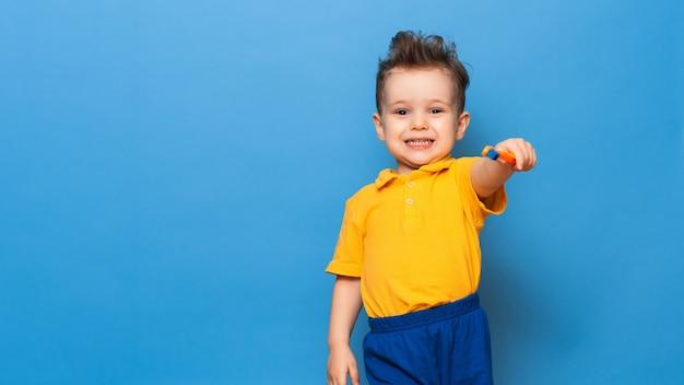 Menino de criança criança feliz escovando os dentes com escova de dentes sobre fundo azul. cuidados de saúde, higiene dentária. maquete, copie o espaço