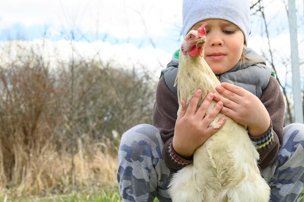 Menino de criança de quatro anos bonitinho segurando nas mãos uma galinha branca na natureza ao ar livre