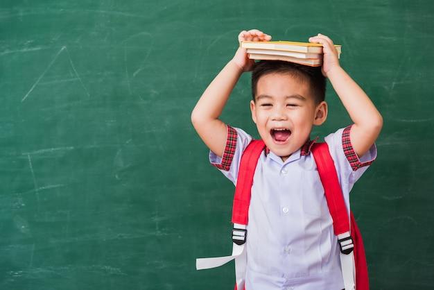 Menino de criança do jardim de infância em uniforme de estudante com mochila e livro na cabeça