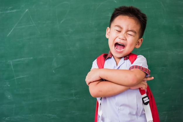 Menino de criança do jardim de infância em uniforme de estudante ficar sorrindo na lousa verde