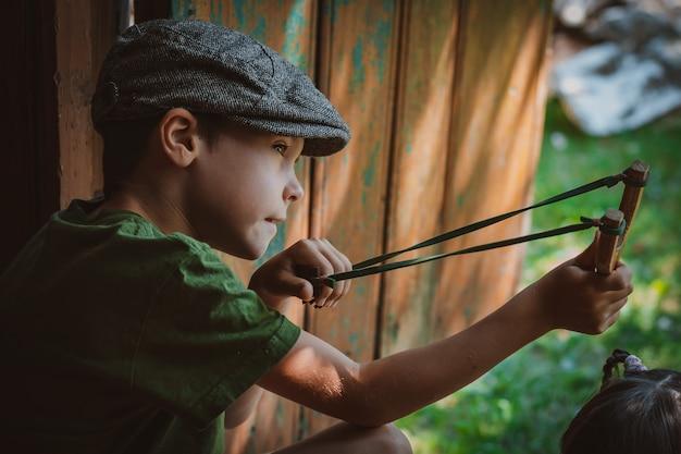 Menino de criança em um boné mira com um estilingue para atirar em um alvo. brincar como uma criança na aldeia de férias.