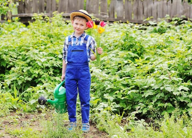 Menino de criança em um chapéu de palha em um jardineiro de terno azul de trabalho com um buquê de tulipas e um regador verde nas mãos, sorrindo para a superfície do jardim