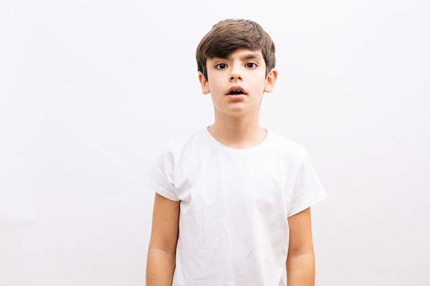 Menino de criança linda vestindo camiseta casual em pé sobre um fundo branco isolado com medo e chocado com a expressão de surpresa, medo e rosto animado.