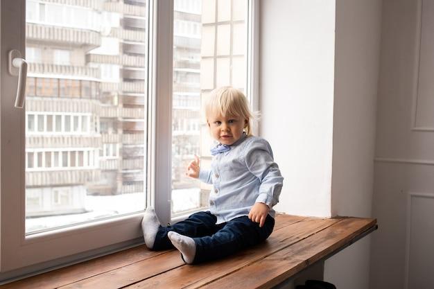 Menino de criança pequena criança sentado na janela. tema coronavirus. ficar em casa.