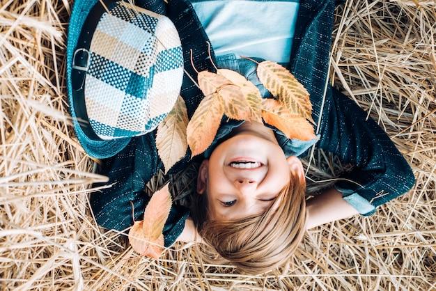 Menino de criança sorridente brincando com folhas e olhando para a câmera encontra-se no feno.