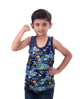 Menino de criança sorridente, mostrando a força dos músculos do bíceps de sua mão.