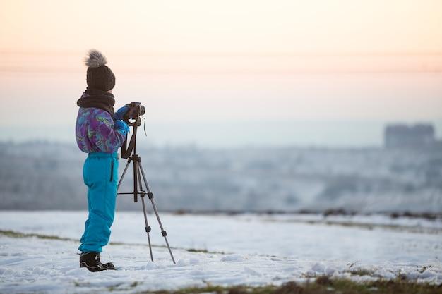 Menino de criança tirando fotos do lado de fora no inverno com câmera fotográfica em um tripé no campo coberto de neve.