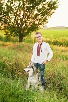 Menino de criança ucraniana com cachorro husky em um campo no verão ao pôr do sol