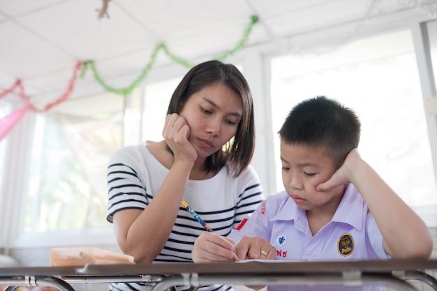 Menino de crianças fazendo lição de casa com a mãe