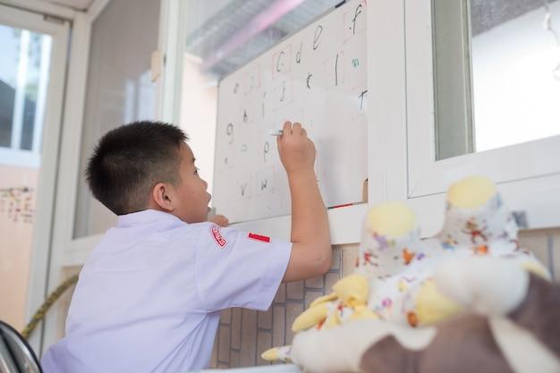 Menino de crianças fazendo lição de casa, garoto escrever papel