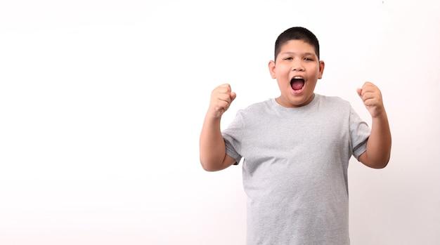 Menino de crianças feliz animado levantando os punhos, fazendo o gesto de sim, comemorando o sucesso em fundo branco.