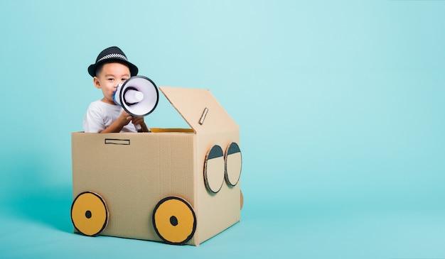 Menino de crianças sorri na condução de carro de jogo criativo por uma imaginação de caixa de papelão com megafone