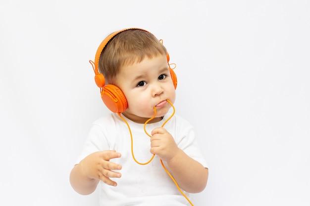 Menino de dois anos em camisa branca com fones de ouvido, isolado no branco
