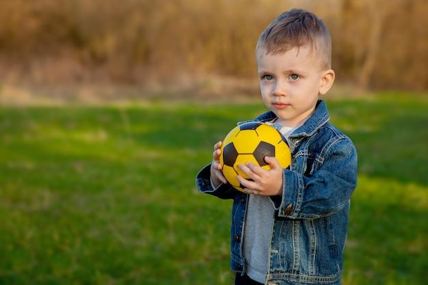 Menino de dois anos mantendo bola de futebol no parque