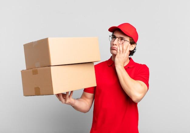 Menino de entrega de pacotes se sentindo entediado, frustrado e com sono depois de uma tarefa cansativa, enfadonha e tediosa, segurando o rosto com a mão