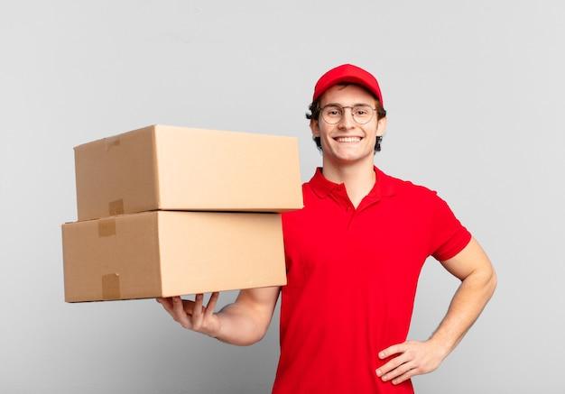 Menino de entrega de pacotes sorrindo feliz com uma mão no quadril e atitude confiante, positiva, orgulhosa e amigável
