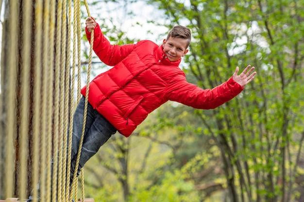 Menino de escola adolescente desfrutando de atividade em um parque de aventura escalada em um dia de primavera